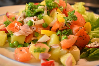 Aardappelsalade met sla, tomaat, doperwten en ham